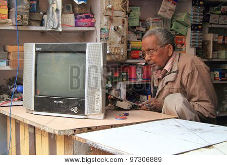 man is repairing tv in repair shop