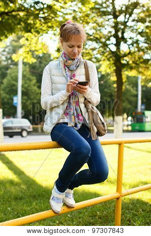 Girl Is Sitting At Fence Railings With Phone In Her Hands
