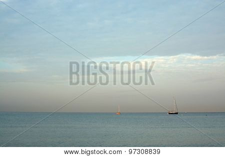 Two Sailboats Moored In Bay At Dawn
