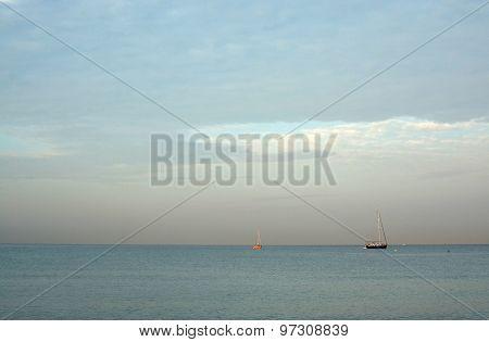 Two Sailboats Moored In Bay At Dawn