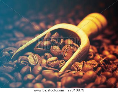 Closeup of coffee beans with wooden scoop.Filtered image: cool cross processed vintage effect.