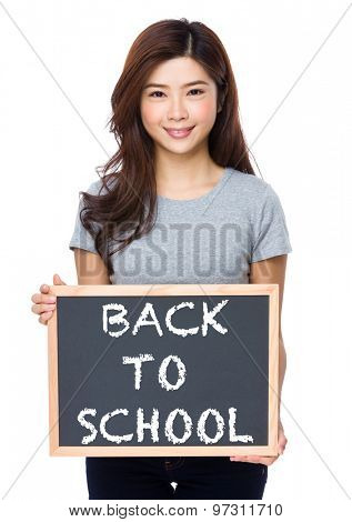 Young woman with chalkboard showing phrase of back to school