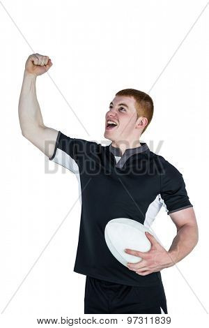 Rugby player gesturing victory while holding a rugby ball