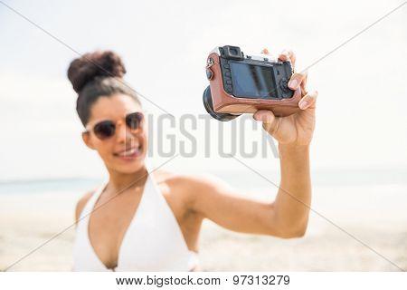Pretty woman in bikini taking selfie at the beach
