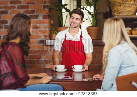 Waiter serving coffees to two customers at the coffee shop