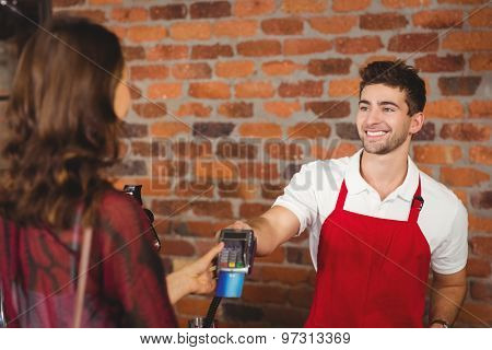 Smiling waiter handing a pin terminal at the coffee shop