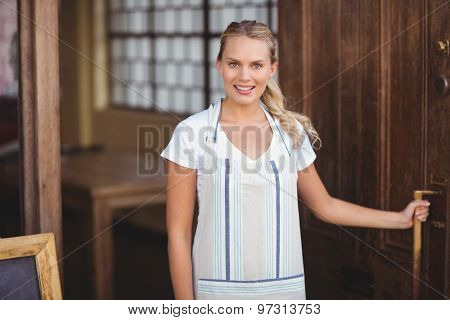 Portrait of smiling blonde waitress opening the door at coffee shop