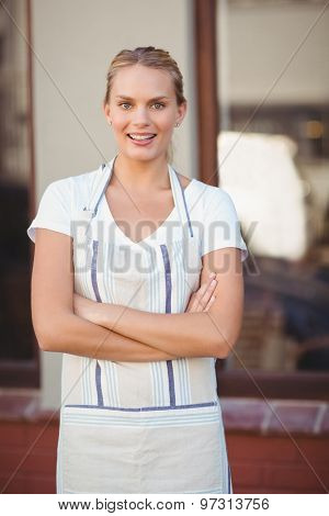 Portrait of smiling blonde waitress with arms crossed at coffee shop