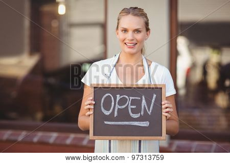 Portrait of smiling waitress showing chalkboard with open sign at coffee shop