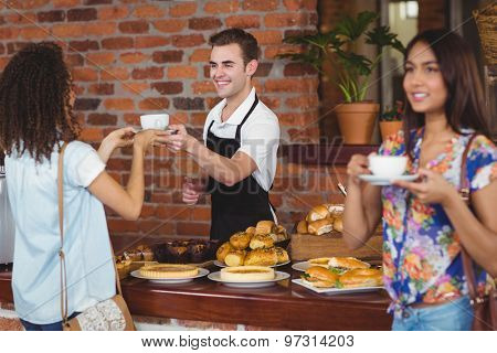 Smiling barista giving coffee to pretty customer at coffee shop