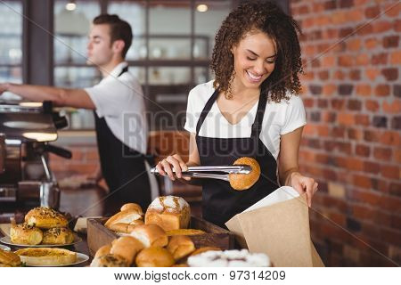 Smiling waitress putting bread roll in paper bag at coffee shop