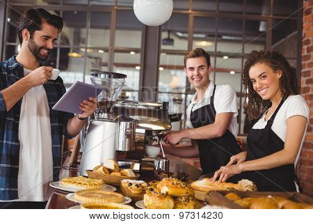 Portrait of smiling colleagues serving customer with tablet and coffee at coffee shop