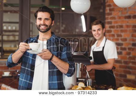Portrait of smiling hipster drinking coffee in front of barista at coffee shop
