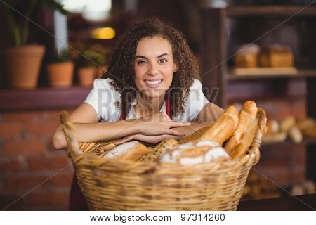 Portrait of a waitress bended over a basket of bread at the coffee shop