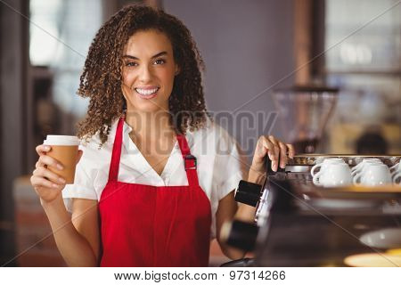 Portrait of a waitress holding a take-away mug at the coffee shop