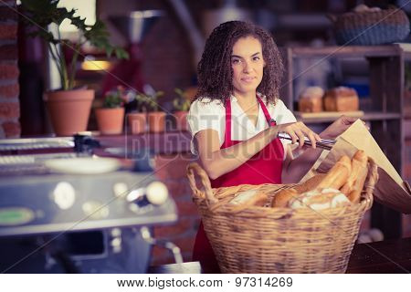 Portrait of a waitress putting bread in a paper bag at the coffee shop