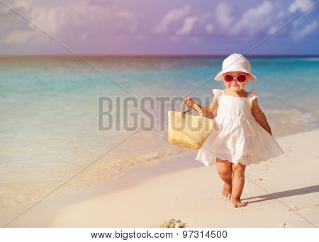 cute little girl walking on summer tropical beach