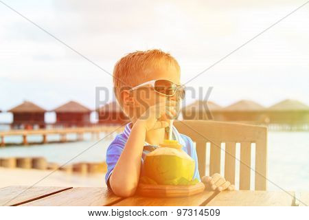 little boy drinking coconut cocktail on tropical beach