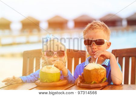 little boy and girl drinking coconut cocktail on tropical beach
