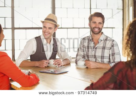 Laughing friends having coffee together at coffee shop