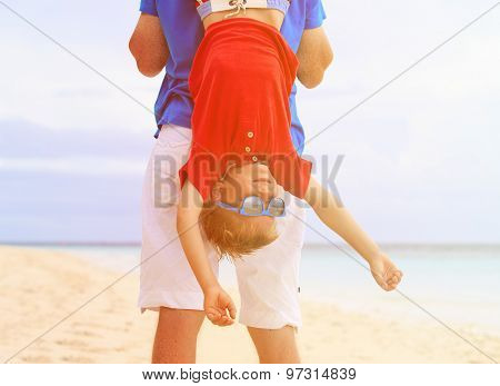 father and little son playing on summer beach