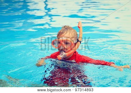 little boy swimming with mask in the pool