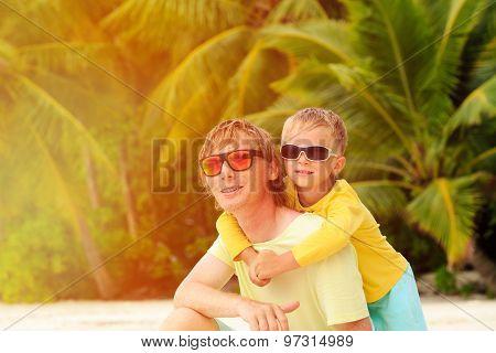 father and little son hug on summer beach