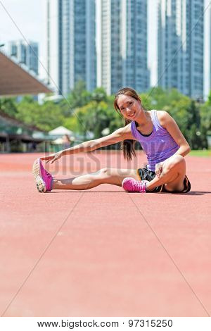 Woman doing warm up exercise in sport stadium
