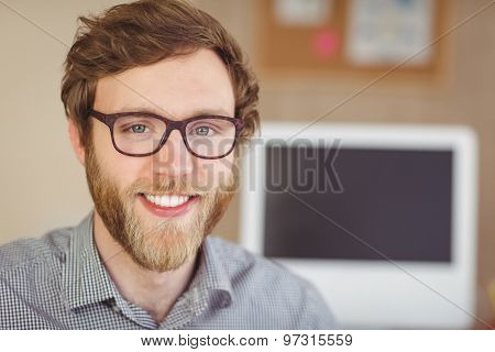 Bearded hipster smiling at camera in his office