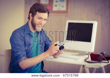 Hipster photographer looking at his camera in his office