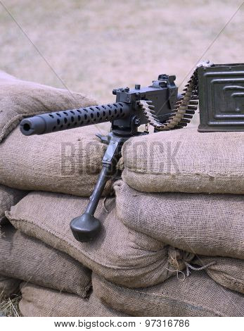 Historic Machine Gun With Bullets Over The Sandbags In Trench