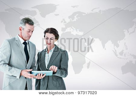 Business people looking at tablet against grey background