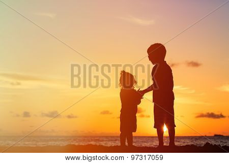 little boy and girl holding hands at sunset