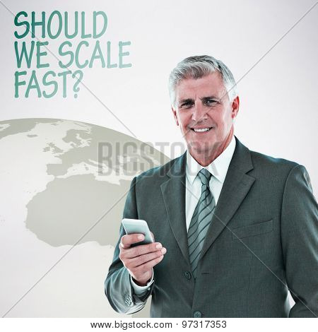 Smiling businessman using his smartphone against grey background