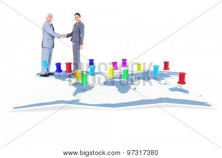 Businessman and woman shaking hands against world map with pointers