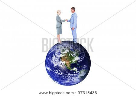 Smiling business people shaking hands against earth
