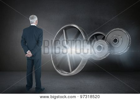 Rear view of mature businessman posing against black wall