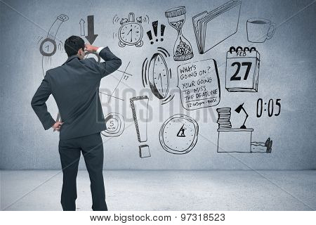 Businessman standing hand on hip against grey room