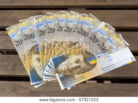 Swiss Francs, Denomination Of  200 On A Wooden Background