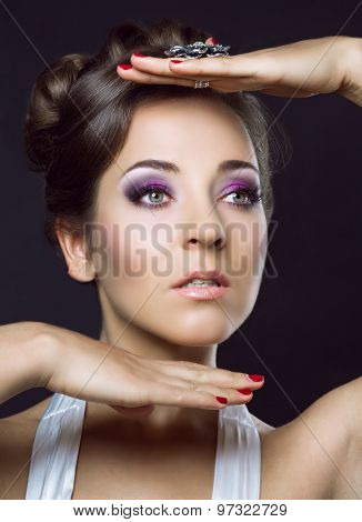 young brunette woman with beautiful makeup and hair, against dark studio back?round