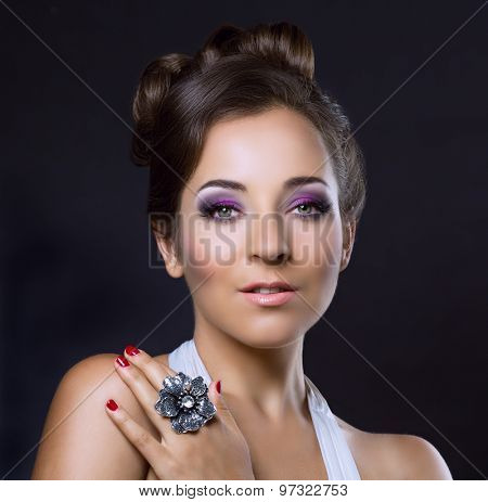 young brunette woman with beautiful makeup and hair, wearing a silver ring