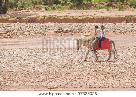 AIT BENHADDOU, MOROCCO - APRIL 10, 2015:  Local boys ride a donkey on riverside near old town of Ait Benhaddou
