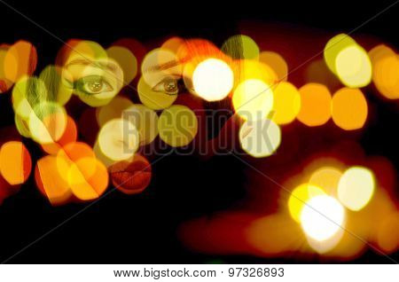 Double exposure photo of female eyes and lips with defocused city lights