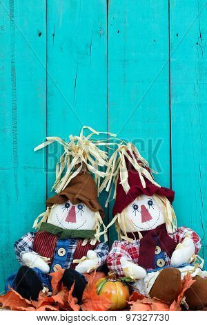 Scarecrows sitting by fence by fall decor
