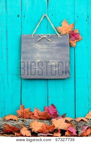 Blank rustic wood sign hanging on fence with fall decor border