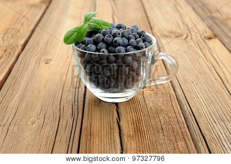 Glass Teacup Full Of Fresh Wild Blueberries With Green Spring On Wooden Table Copyspace