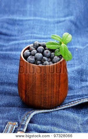 Fresh Wild Blueberries In Wooden Vase With Wooden Spoon On Old Indigo Jeans