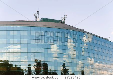 Glass facade of office building with cell tower