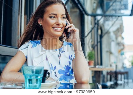 Young Woman At Sidewalk Cafe Talking On The Mobile Phone