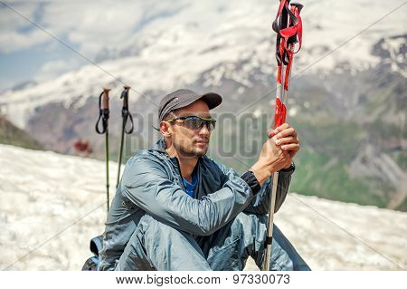 Man Mountaineer Sitting On Hillside Of Mount Cheget